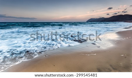 Stones, sea foam and sky at the sunset in the beach - stock photo