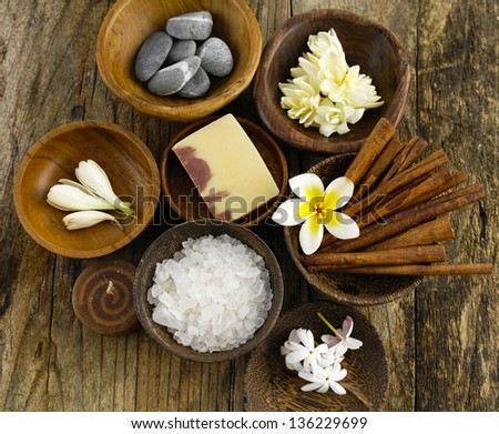 Stones, soap, salt, cinnamon, frangipani flower in wooden bowl on old wood