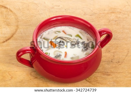 Stoneware pot of oyster chowder on rustic wooden counter top. - stock photo