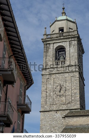 Stony bell tower of Basilica of San Giacomo in Belaggio on the background of blue sky with gentle clouds