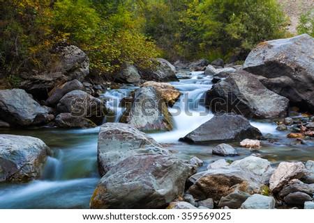 Stony bottom of the mountain river. Cascade waterfalls. Altai Mountains, Russia. . Beautiful landscape. Summer landscape. Mountain landscape. Beautiful  waterfalls. Waterfalls  - stock photo