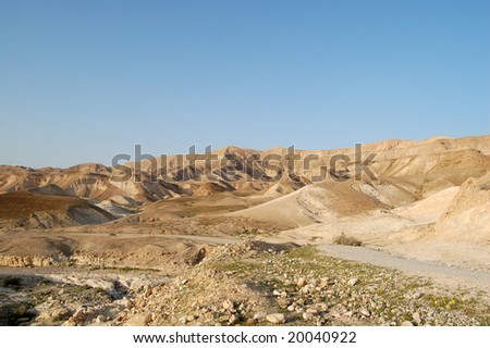 Stony desert, river channel and dirt road