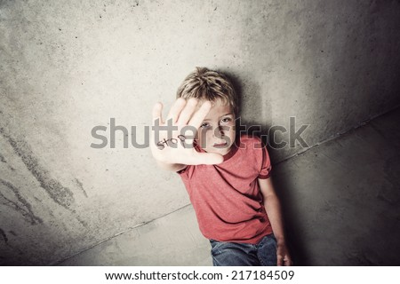 Stop abuse.  Focus on boy's face. - stock photo