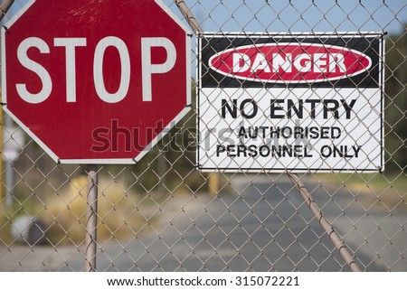 Stop and Danger sign at secured gate of property, no entry, trespassing, blurred background, copy space. - stock photo