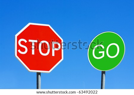 Stop and Go sign against a blue sky - stock photo