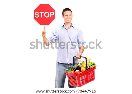 Stop and shop here A male holding a full shopping basket and a stop road sign isolated on white background - stock photo
