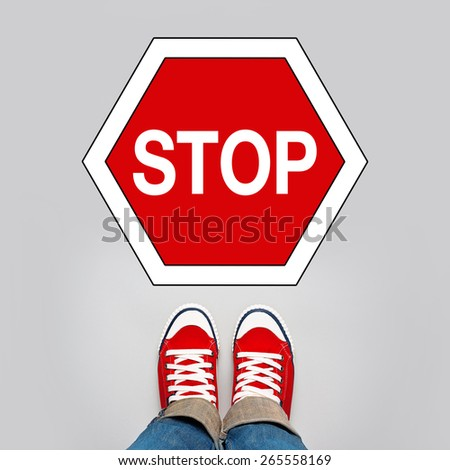 Stop Concept, Young Teenage Person in Red Sneakers Standing in Front of Stop Traffic Sign, top view - stock photo