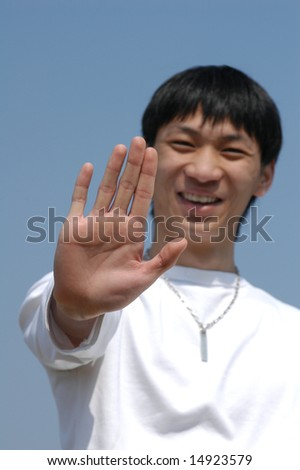 Stop do it now! Young Asian man holding hand up saying 'Stop' or 'No' - palm in focus - stock photo
