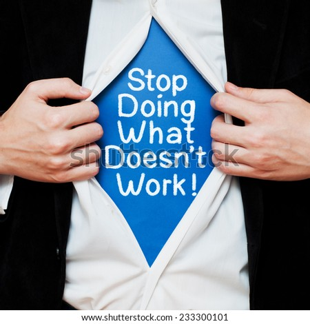 Stop Doing What Doesn't Work ! Efficiency concept. Businessman showing a superhero suit underneath his shirt with a message written on it - stock photo