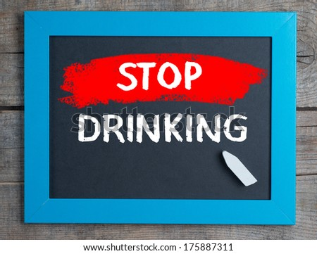 Stop Drinking. Creative composition with the message Stop Drinking on blackboard on wooden table - stock photo