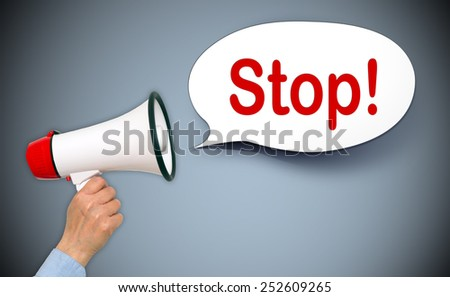 Stop ! - Female hand with megaphone and speech bubble - stock photo
