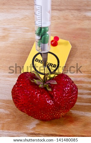 "Stop GMO concept shot. Genetic food engineering concept with a fresh red strawberry on a wooden background, syringe with capsules and ""Do not disturb"" label/Stop GMO with strawberry 2 - stock photo"
