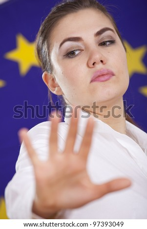 stop hand sign from a woman standing over european flag - stock photo