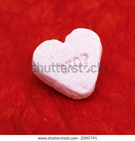 stop (in the name of love)  pink candy heart with the word 'stop' on a red background - stock photo