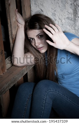 Stop it! Top view of terrified young woman crying and stretching out hand while leaning at the dark wall - stock photo