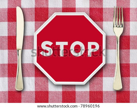 stop on tablecloth with knife and fork - stock photo