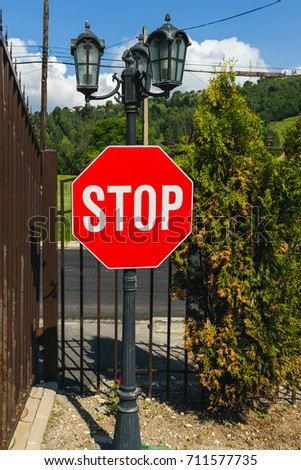 Stop red sign before the entrance with metal gates.