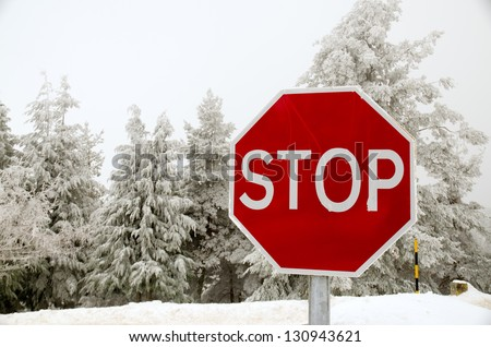 Stop road sign in snowy day in winter. - stock photo