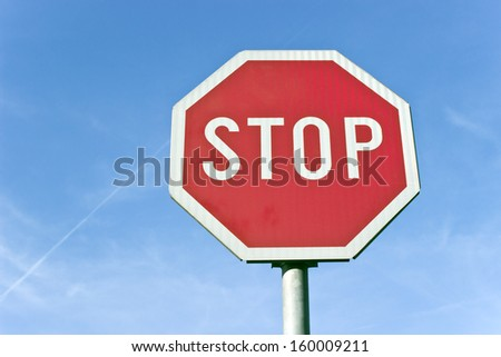 Stop road traffic sign over blue sky - stock photo
