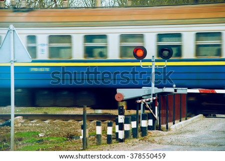 Stop semaphore signal at a railway crossing and a train - stock photo