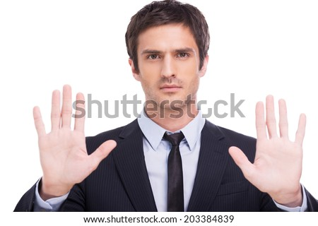 Stop! Serious young man in formalwear looking at camera and showing his palms while standing isolated on white background