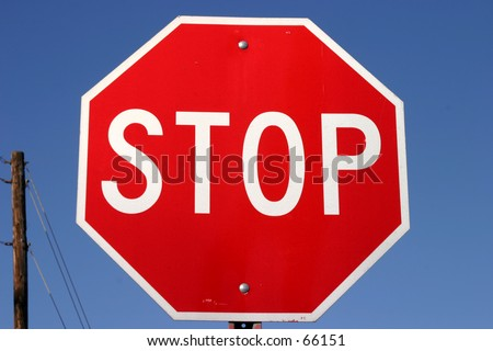 stop sign against a blue sky day