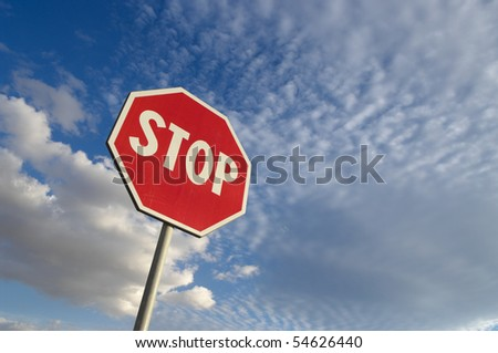 stop sign against blue sky and white clouds - stock photo