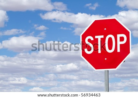 Stop sign against blue sky with clouds