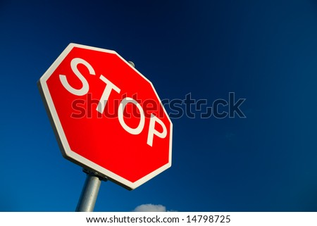 Stop sign against deep blue sky.