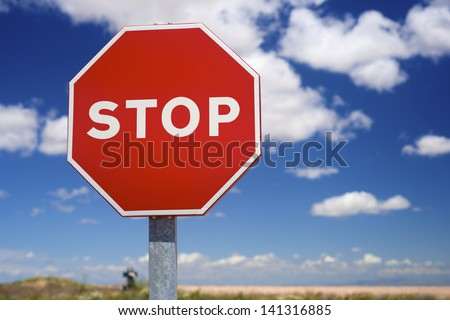 Stop sign and blue sky with white clouds - stock photo