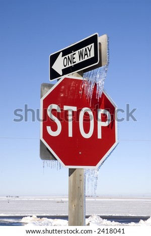 Stop sign and one way sign on wooden post with icicles and blue sky in background