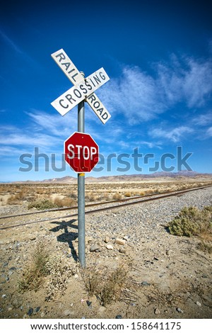 Stop sign and Railroad crossing keep vehicles safe crossing an isolated stretch of rails in the Mojave Desert.