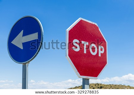 Stop sign and signal direction compulsory against the sky in Spain