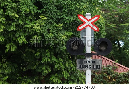 """Stop sign at a cross with railway train. The words in sign mean """"Red light, stop"""". - stock photo"""