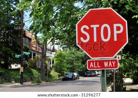 Stop sign at an intersection with a street in the background - stock photo
