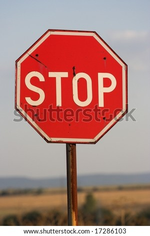 Stop sign at country crossroad - stock photo
