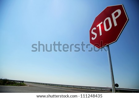 Stop sign by the side of the road - stock photo