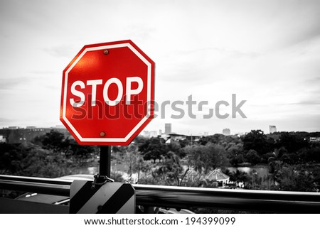Stop sign in a black and white image with City Landscape.