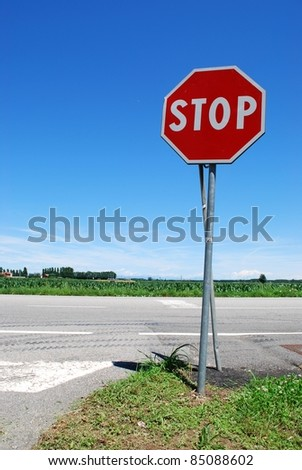 Stop sign in a country road on blue sky - stock photo