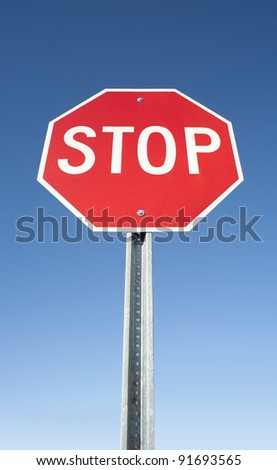 Stop sign in perspective on blue sky background - stock photo