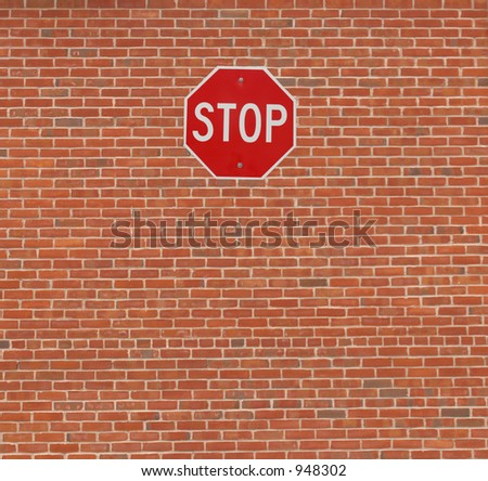 Stop sign on brick wall. - stock photo