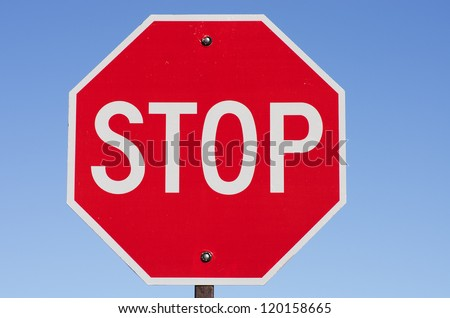 stop sign on metal post with blue sky background