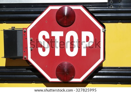 Stop sign on the side of a typical yellow school bus - stock photo