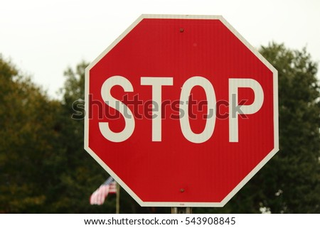 STOP SIGN WITH AMERICAN FLAG IN THE BACKGROUND