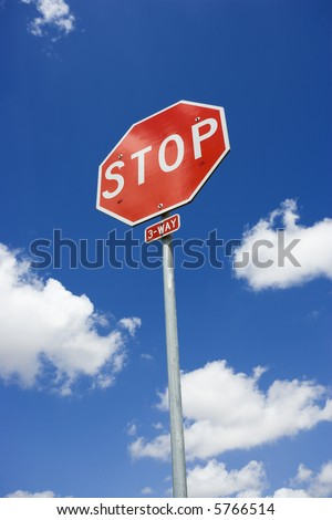 Stop sign with blue cloudy sky.