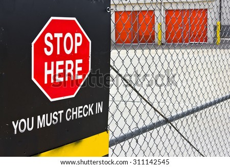 Stop sign with check in posted on a metal fence. - stock photo