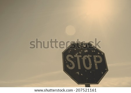 Stop sign with holes from bullets - stock photo