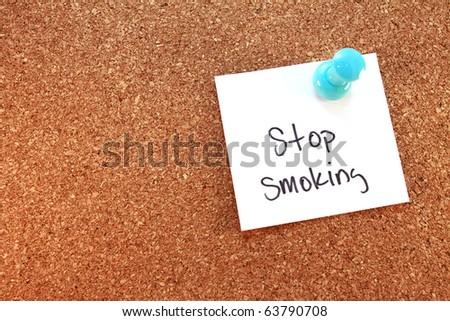 Stop Smoking A stop smoking note tacked on corkboard. Horizontal. - stock photo