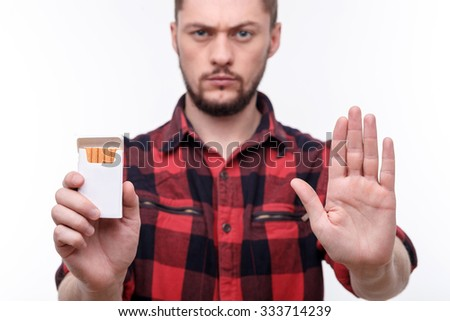 Stop smoking. Attractive young man is holding a pack of cigarettes. He is standing and making refusing gesture. The man is looking at camera seriously - stock photo
