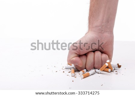 Stop smoking. Close up of male hand breaking cigarettes with his fist. Isolated and copy space in left side - stock photo